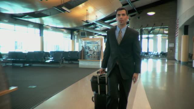 ms ds businessman walking through airport terminal, appleton, wisconsin, usa - appleton video stock e b–roll