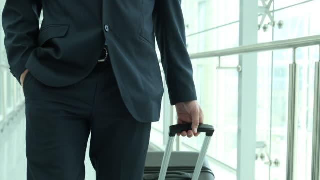 businessman walking through airport terminal - suitcase stock videos & royalty-free footage