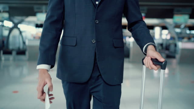 businessman walking through an airport with his luggage - full suit stock videos & royalty-free footage