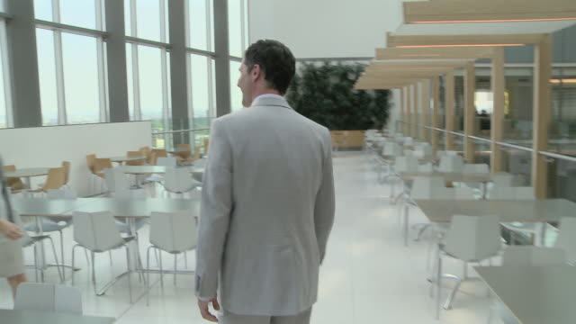 Businessman walking through canteen and shaking hands with businesswoman