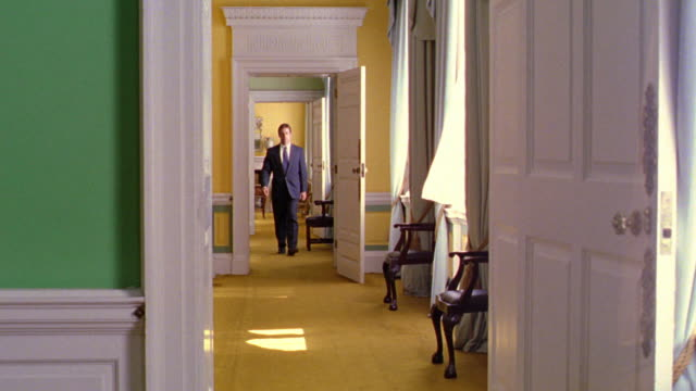 businessman walking through connecting rooms in dublin castle toward + past camera / dublin, ireland - 宮殿点の映像素材/bロール