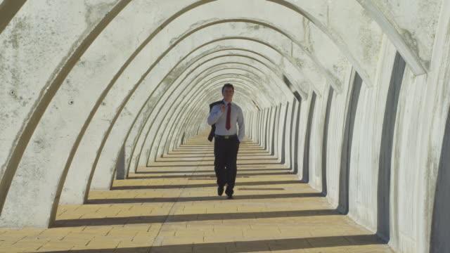 vídeos de stock, filmes e b-roll de ws zi businessman walking through gallery of concrete arches / malaga, malaga, spain  - ir adiante