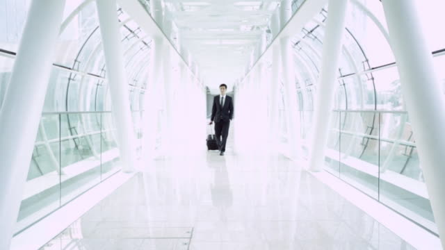 WS Businessman walking through modern airport.