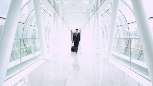 vidéos et rushes de ws businessman walking through modern airport. - accueil entreprise
