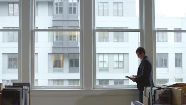 ms r/f businessman walking through office after working on digital tablet near window - 僅一男人 個影片檔及 b 捲影像
