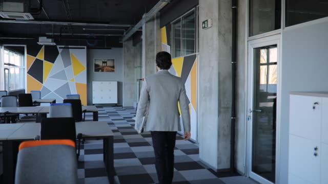 vídeos y material grabado en eventos de stock de empresario caminando por la oficina - con la espalda dando a la cámara