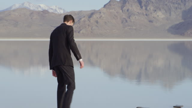 stockvideo's en b-roll-footage met ms ts businessman walking to end of stone pathway in lake stopping and looking at landscape - de volgende stap
