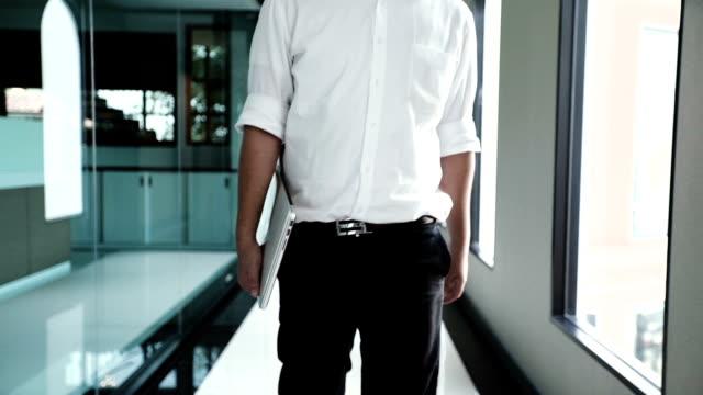 vídeos de stock e filmes b-roll de businessman walking to work with his laptop in the office. - entrada de edifício