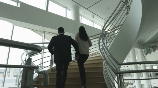 businessman walking up spiral staircase in office - spiral staircase stock videos & royalty-free footage