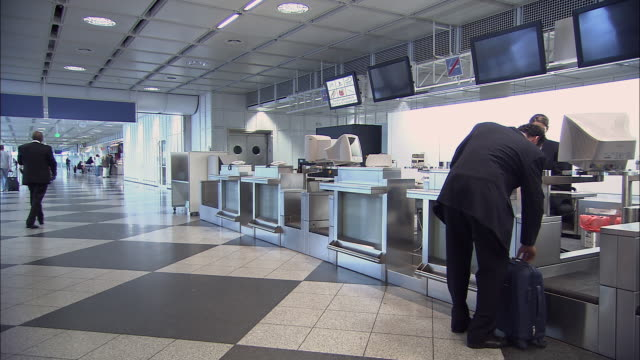 ws pan businessman walking up to airport check-in, checking bag, and walking away as attendant points toward gate/ munich, germany - airline check in attendant stock videos and b-roll footage