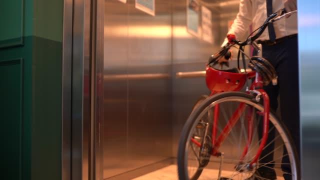 affärsman walking med cykel på moderna kontor - ansvarsfullt företagande bildbanksvideor och videomaterial från bakom kulisserna