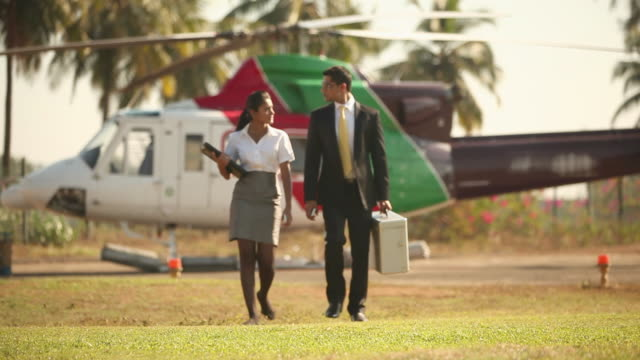 Businessman walking with his secretary in front of a private airplane
