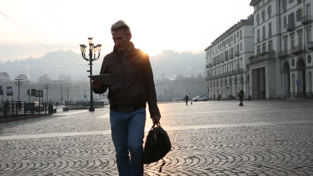 Businessman walks across piazza, looking at digital tablet