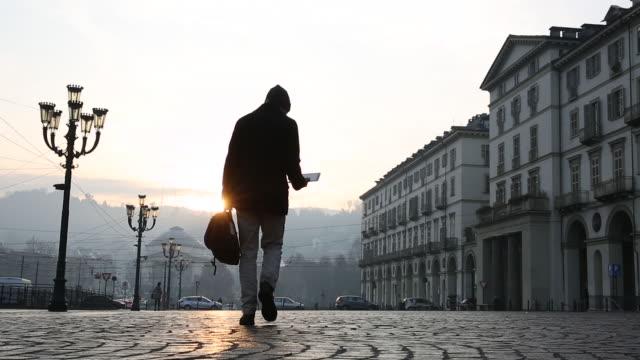 Businessman walks across piazza, looking at digital tablet