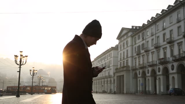businessman walks across piazza, texting on smart phone - piedmont italy stock videos & royalty-free footage