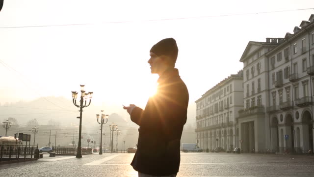 Businessman walks across piazza, texting on smart phone
