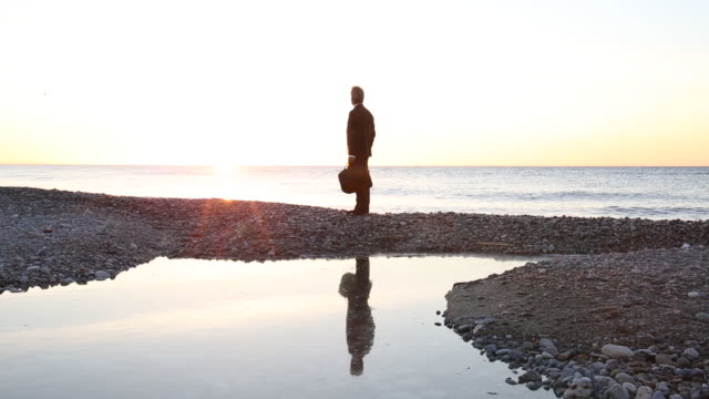 businessman walks along beach at sunrise, looks over sea - horizon stock videos & royalty-free footage