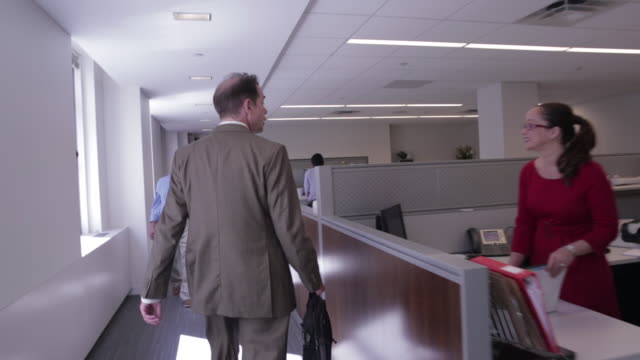 Businessman walks and greets colleagues in office hallway