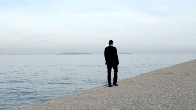 Geschäftsmann geht am Strand
