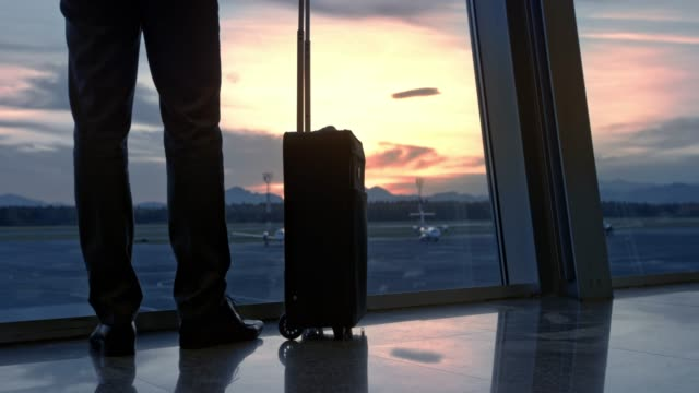 businessman walks up to the glass wall at the airport to watch the sunset and then walks away - wheeled luggage stock videos and b-roll footage