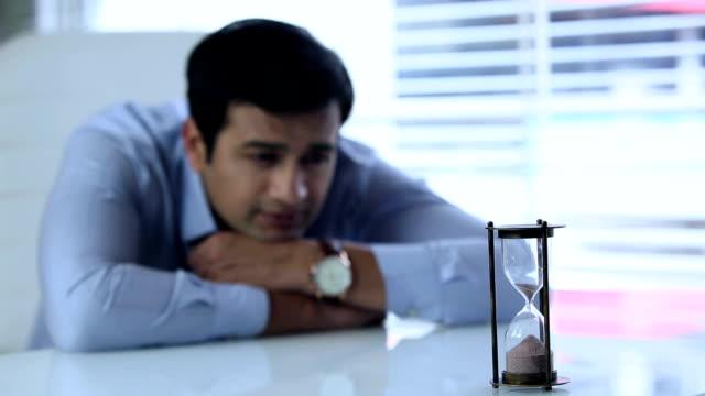businessman watching hourglass, delhi, india - hemd und krawatte stock-videos und b-roll-filmmaterial
