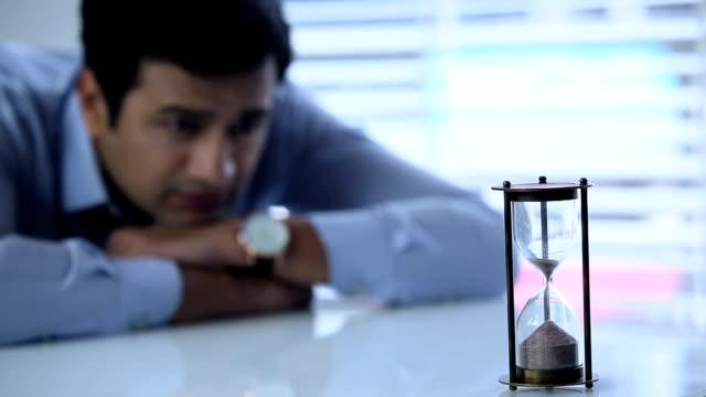 Businessman watching hourglass, Delhi, India
