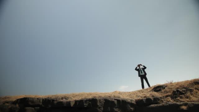 Businessman watching mountains through binoculars