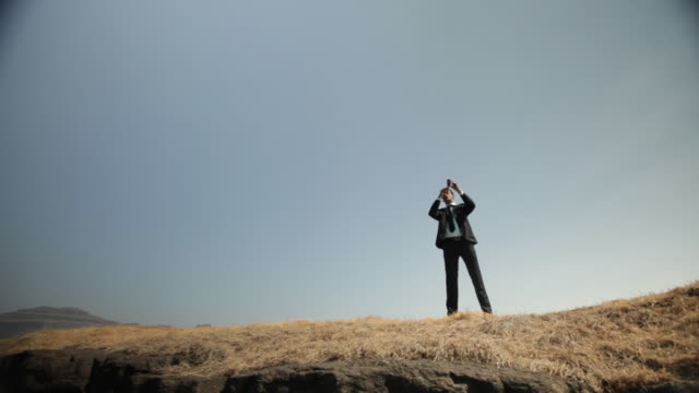 Businessman watching mountains through day telescope