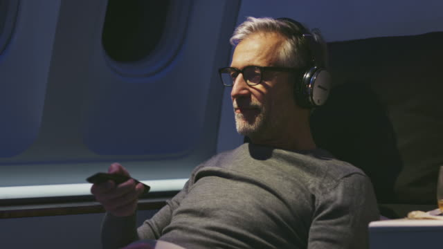 businessman watching movie in private airplane - only men stock videos & royalty-free footage