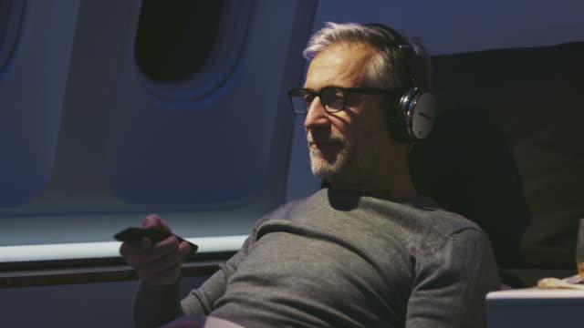 vídeos y material grabado en eventos de stock de hombre de negocios viendo películas en avión privado - pasajero