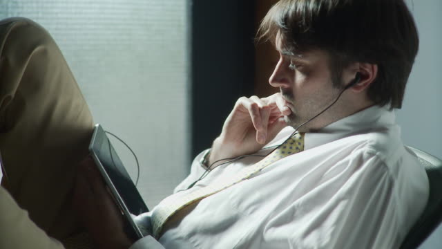 MS Businessman watching movie on digital tablet / Brooklyn, New York, USA