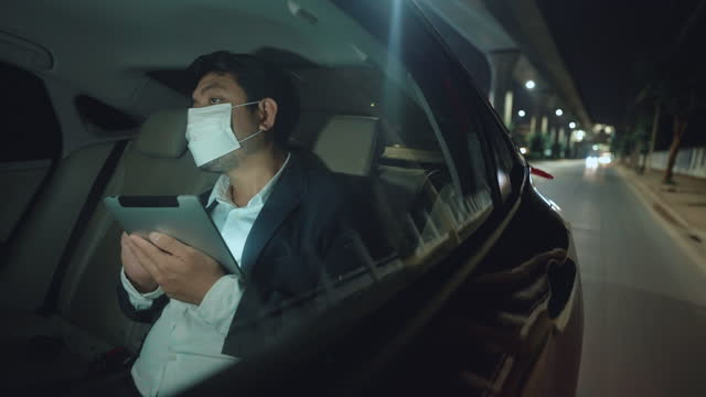 businessman wear protective face mask working on the digital tablet and explain a location to the car - taxi stock videos & royalty-free footage