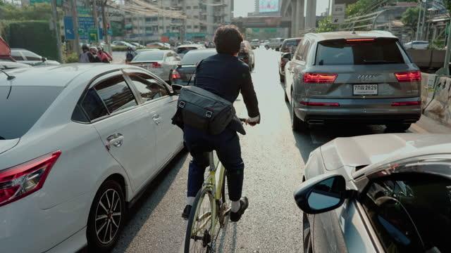 vídeos de stock, filmes e b-roll de empresário usa máscara cirúrgica enquanto anda de bicicleta na cidade. - a caminho