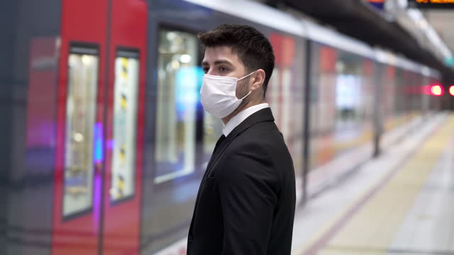 businessman wearing a face mask in underground station - underground station platform stock videos & royalty-free footage