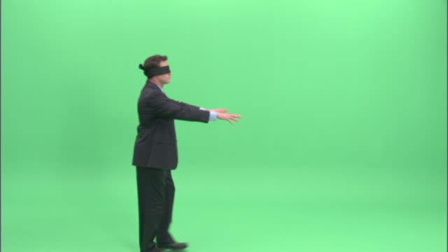 WS, Businessman wearing blindfold walking aimlessly in studio