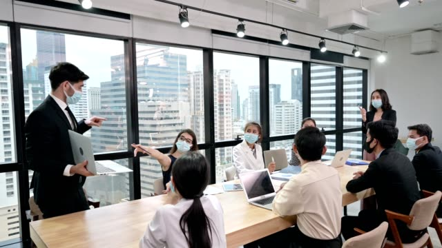 vídeos de stock e filmes b-roll de businessman wearing face mask with presentation of business plan on laptop. corporate business meeting in modern office - conferência de imprensa