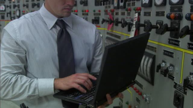 vídeos de stock, filmes e b-roll de cu tu businessman wearing hard hat and typing on laptop while monitoring gauges in control room / vista del mar, california, usa - camisa e gravata
