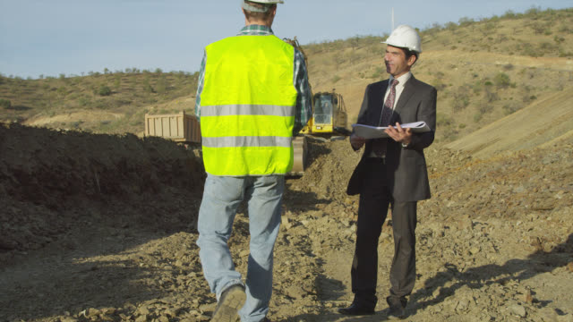 businessman wearing hard hat standing in construction site looking at plans with earth moving equipment operating in background, workman enters frame right, they shale hands and discuss the plans