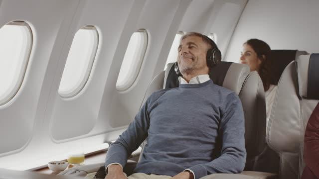 vídeos de stock e filmes b-roll de businessman wearing headphones in private jet - encostado