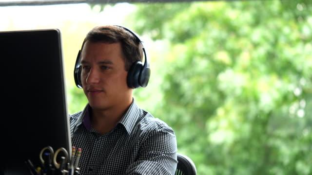 vidéos et rushes de cu businessman wearing headphones while working on computer at workstation in office - un seul homme d'âge moyen