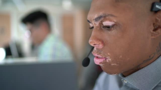 stockvideo's en b-roll-footage met zakenman die hoofdtelefoons draagt terwijl het spreken en het werken aan laptop in modern bureau - menselijke huid