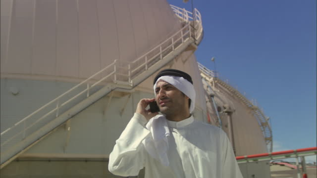 LA MS Businessman wearing keffiyeh and talking on cell phone near oil storage tank at refinery / Vista del Mar, California, USA