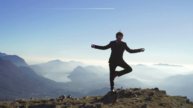 businessman wearing suit doing a yoga tree pose on top of a mountain (vrikshasana) - offbeat stock videos & royalty-free footage
