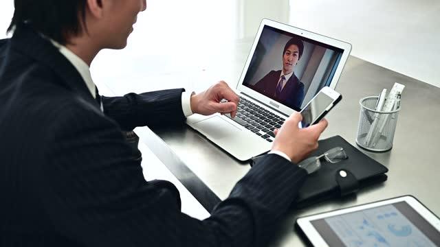 一個穿西裝的商人正在辦公室做在線會議 - 偏遠的 個影片檔及 b 捲影像