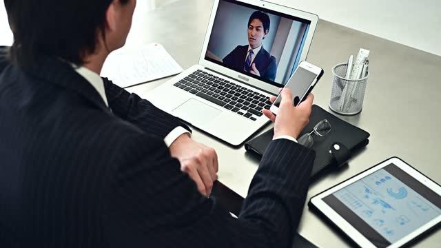 スーツを着たビジネスマンがオフィスでオンライン会議をしています - 離れた点の映像素材/bロール