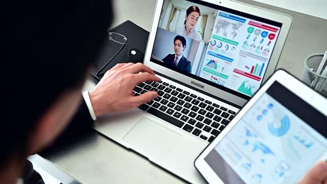 スーツを着たビジネスマンがオフィスでグループとオンラインミーティングをしています - マネージャー点の映像素材/bロール