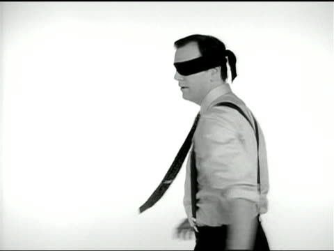 A businessman wearing suspenders and blindfold turns around in circles and reaches out.