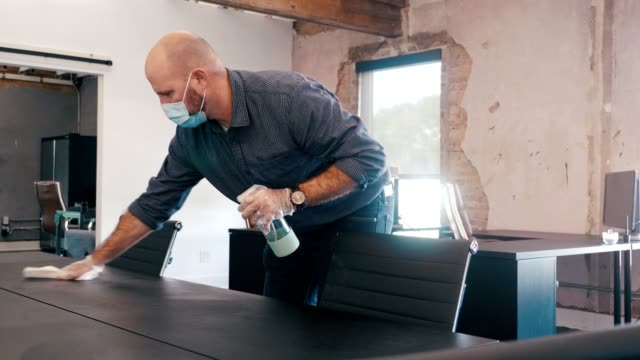 businessman wears protective mask while cleaning conference table - wearing a towel stock videos & royalty-free footage