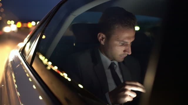 MS Businessman wind down a window of a limousine driving in the city at night
