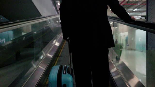 geschäftsmann mit einem blauen koffer, gehen sie zum check-in-schalter airline airport. - stufen stock-videos und b-roll-filmmaterial